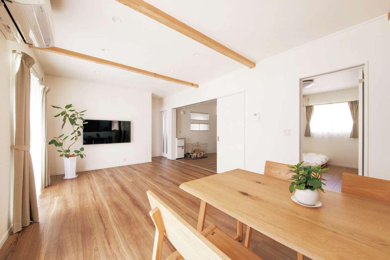Um House(マル祐戸田建築)【間取り、ペット、平屋】各部屋のドアを開け放てば、家中がワンルームのように繋がる。ダイニングテーブルの対角線上に、室内で飼うチワワのケージが見える