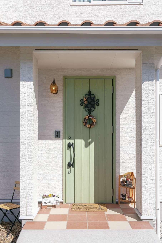 Um House(マル祐戸田建築)【デザイン住宅、間取り、屋上バルコニー】さわやかなグリーンの玄関扉に季節のリーフを飾ってゲストをお出迎え。オリーブの木や色とりどりの花がガーデンを彩る