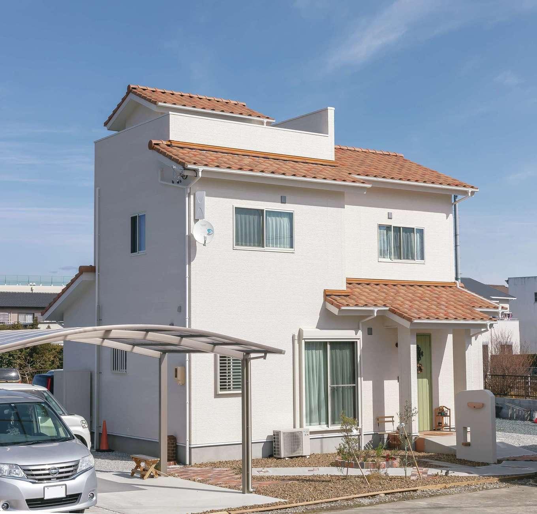 Um House(マル祐戸田建築)【デザイン住宅、間取り、屋上バルコニー】白壁とオレンジ色のテラコッタ瓦が青空に映える、南欧プロヴァンス風のかわいらしい外観。屋上にあるスカイバルコニーに続く階段室の屋根がちょこんと見えるユニークなデザイン