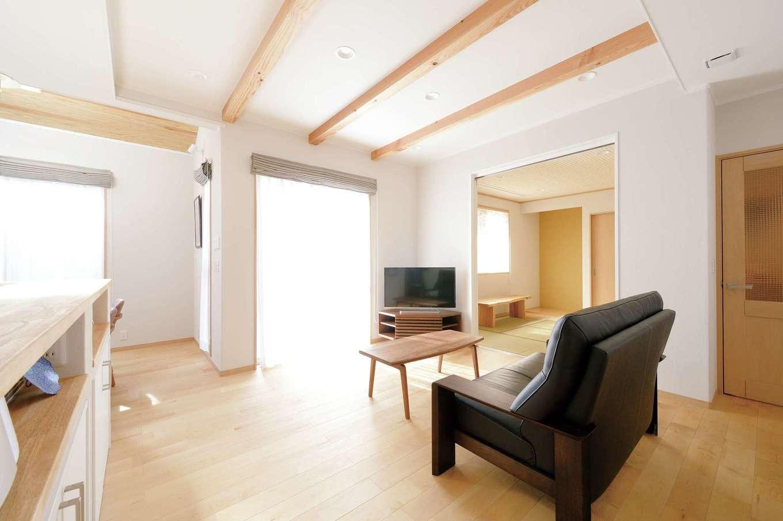 ほっと住まいる【子育て、趣味、自然素材】LDKと和室が緩やかにつながった1階の居住スペース。塗り壁など自然素材がすっきりした空気を保つ。アイランドキッチンからは常に家族の様子が見渡せるので安心