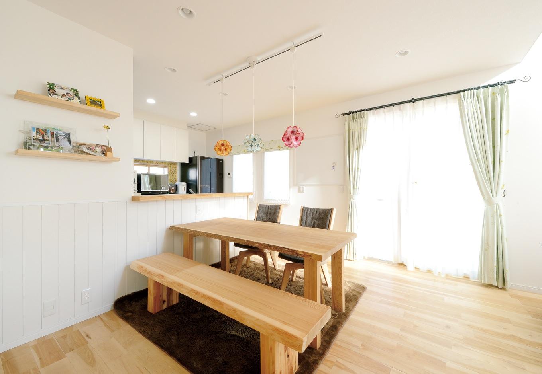 ほっと住まいる【子育て、輸入住宅、省エネ】カントリースタイルの対面キッチン。カラフルなペンダントライトは、貝殻を薄くスライスした素材からできている。タモのダイニングテーブルとベンチは杉山社長からの新築祝い
