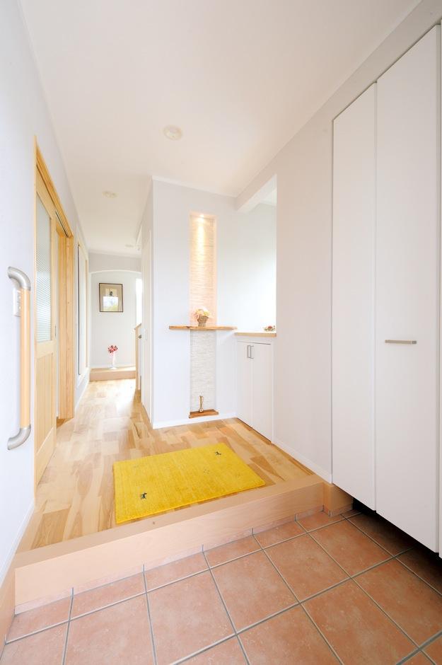 ほっと住まいる【輸入住宅、自然素材、省エネ】奥まで視線が伸び、開放感のある玄関。キッチンに使用したのと同じモザイクタイルがアクセントに