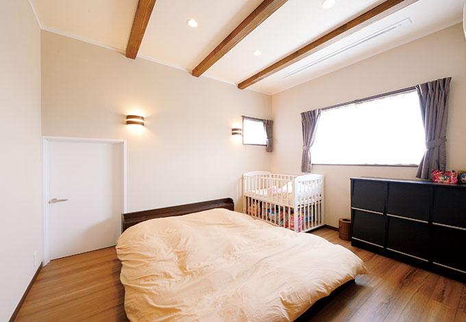ほっと住まいる【収納力、二世帯住宅、自然素材】2階にある子世帯の寝室も調湿効果に優れたシラス壁を採用。ダークブラウンを基調としたシックな空間。低い扉の奥は小屋裏収納