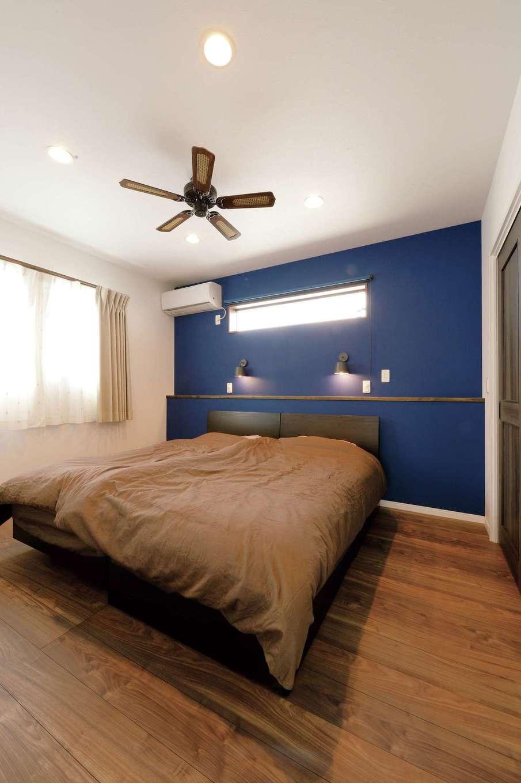 ほっと住まいる【自然素材、省エネ、間取り】主寝室はご主人の大好きなネイビーのクロスをアクセントウォールに。落ち着きのあるダークブラウンの床がリラックス効果を高めている
