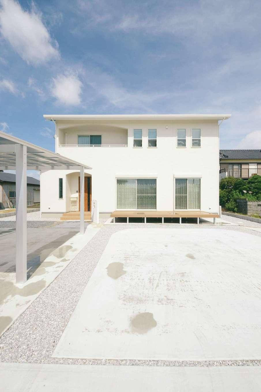 ほっと住まいる【子育て、自然素材、間取り】真っ白な外観に木目調の玄関が映える。2階はベランダの垂れ壁をRにし、上げ下げ窓を採用することで外観もかわいらしく