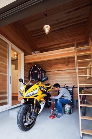 花みずき工房【収納力、趣味、ガレージ】ロフト付きのビルトインガレージ 玄関ホールと行き来できるバイクガ レージは壁に準不然の杉板を使用。 ロフトを設けたことで収納力が増し、 作業スペースも余裕の広さに