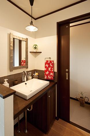 花みずき工房|トイレと洗面台を並べてスムーズな動線を実現。トイレの出入り口の向きを変え、さらにドアから引き戸に変更。洗面台は照明やタイルに凝って、おしゃれに造作した