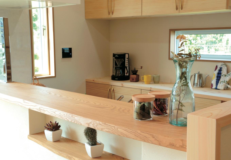 住まいるコーポレーション【デザイン住宅、自然素材、省エネ】対面式のキッチンには、木目が優美なタモの無垢カウンターを設置。カウンターの下のニッチも同じタモ材