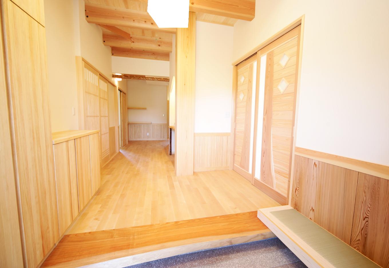 住まいるコーポレーション【和風、二世帯住宅、自然素材】造り付けの玄関ベンチは、靴の脱ぎ履き時にとても便利。背もたれには浮づくりの秋田杉を使用している