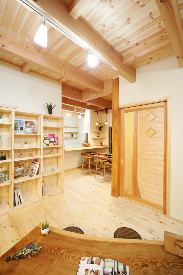 住まいるコーポレーション【収納力、和風、自然素材】リビングへ緩やかに繋がるダイニングキッチン。天井の太い梁や杉の無垢のカウンター、オリジナルのテーブルから木の魅力がたっぷりと伝わってくる