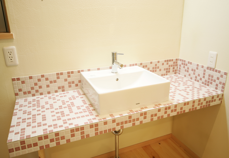 住まいるコーポレーション【収納力、和風、自然素材】奥さまこだわりの洗面スペース。壁にはピンク系のモザイクタイルを貼り、華やかでスイートな雰囲気に仕上げた