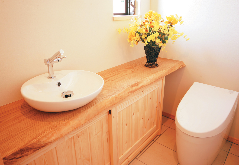住まいるコーポレーション【和風、自然素材、省エネ】造り付けカウンターを設けたトイレ。カウンターには無垢のくりの板を使用している