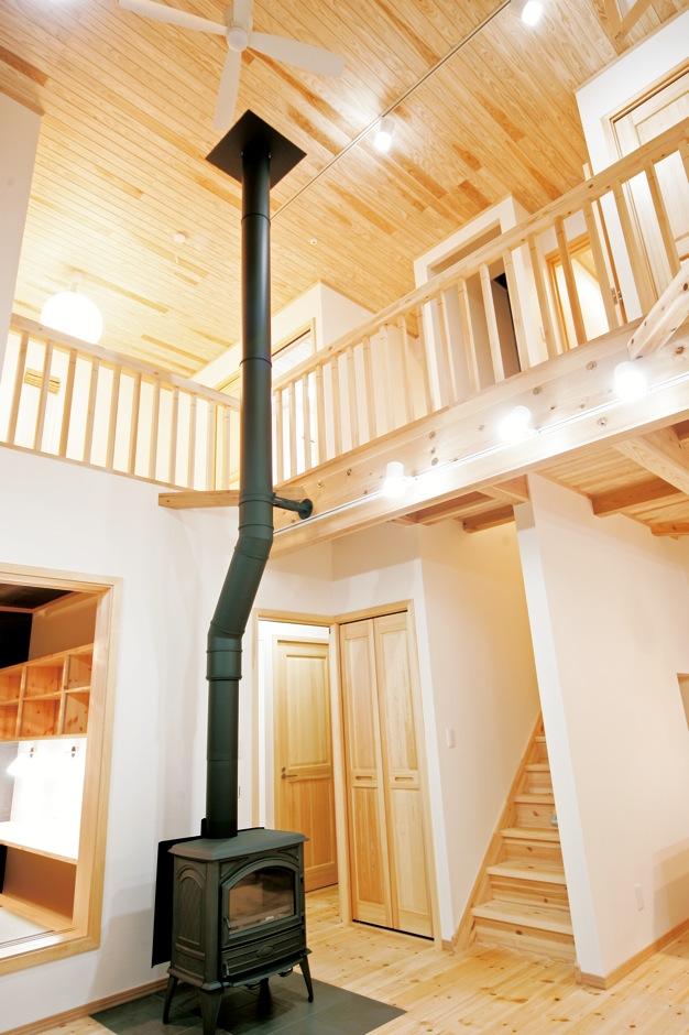 住まいるコーポレーション【自然素材、省エネ、間取り】吹抜け空間に真っ直ぐ伸びた薪ストーブの煙突が、縦の広がりをいっそう強調している