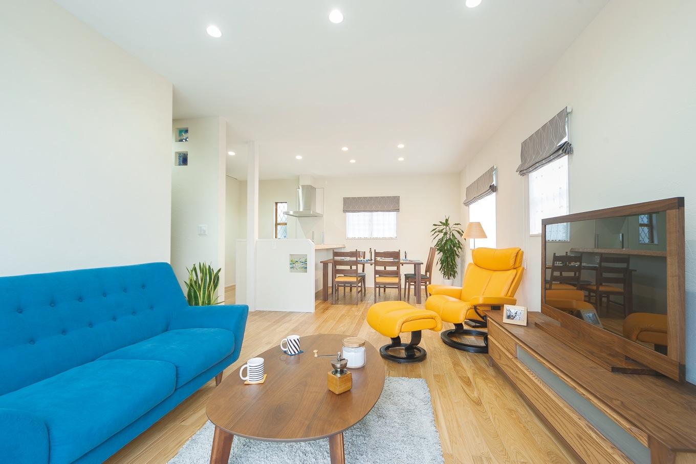 住まいるコーポレーション【デザイン住宅、省エネ、インテリア】タモ材の床と珪藻土の壁で仕上げたLDK。自然素材の心地よさが家族を優しく包みこむ。「暮らしに色を活かしたい!」との奥さまの要望でコーディネートしたポップなカラーのソファが、シンプルな空間によく映える。キッチンの壁やカウンターの腰壁には工芸作家の 創作ガラスを埋め込み、個性豊かな彩りをプラス