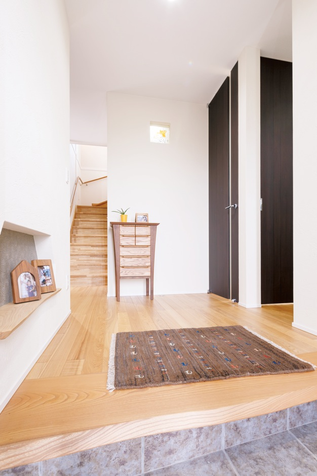 住まいるコーポレーション【デザイン住宅、省エネ、インテリア】玄関にはゆとりのスペースを確保。玄関の上り框(かまち)には耳付きのケヤキ材を用い、自然木の美しい曲線を空間デザインに活かしている。ニッチや正面の創作ガラスが珪藻土に映える。また、1階には260cm、2階には240cmのハイドアを用いることで、縦の広がりを強調した。土間の横にはシューズクローゼットもある