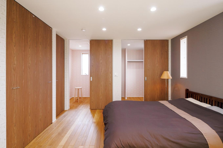 住まいるコーポレーション【デザイン住宅、省エネ、インテリア】タモ材の床と珪藻土の塗り壁が体に優しい自然素材の寝室。人生の3分の1は睡眠であることを考えれば、寝室の内装にもこうしてこだわりたいもの。ウォークインクローゼットや納戸もたっぷり設けてある。収納スペースの中のピンク色のクロスは、こげ茶色の木目と相性バツグン