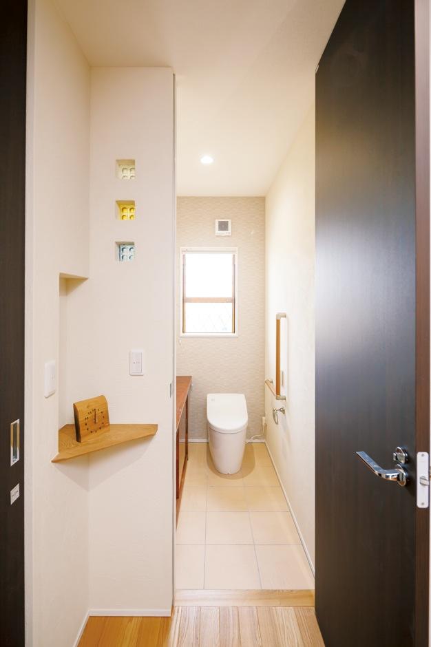 住まいるコーポレーション【デザイン住宅、省エネ、インテリア】トイレのドアにも260cmのハイドアを使用。トイレの横の壁にはガラスブロックを3つ並べ、その下に三角形のニッチを設置。隅っこの何気ない空間を上手に活かして、オシャレに演出している