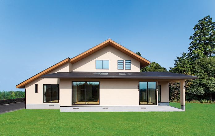 住まいるコーポレーション【デザイン住宅、自然素材、省エネ】緑ゆたかな周囲の風景と調和した大屋根の外観。建物を東西に長く配置したことで、南面の窓から室内にたっぷり日が注ぐ。深い庇が夏の直射日光を防ぎ、涼しい日陰をもたらす一方で、冬は斜めから射す陽光を室内の奥まで採り入れられる