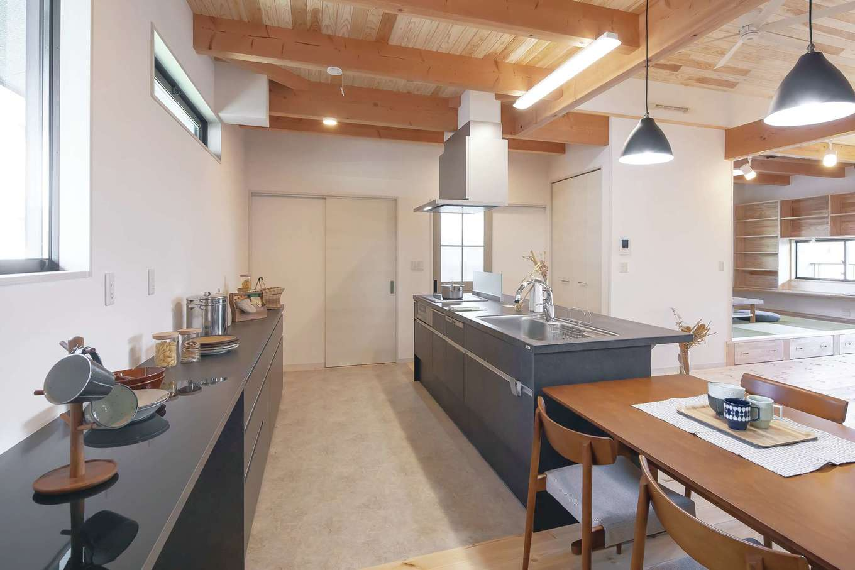 住まいるコーポレーション【自然素材、夫婦で暮らす、間取り】2階のキッチンはブラックの乾漆風の扉とカウンターで統一。ワークスペースを広々と設け、家族一緒にクッキングを楽しめる空間に。キッチンの奥にはパントリー、正面にはファミリークローゼットが設けてある
