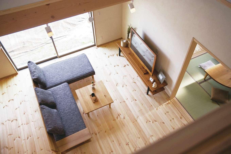 住まいるコーポレーション【デザイン住宅、自然素材、間取り】2階の廊下からLDKを眺める。吹抜けを通じて上下階がつながり、家族の気配を常に感じながら安心して過ごすことができる