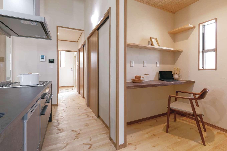 住まいるコーポレーション【デザイン住宅、自然素材、夫婦で暮らす】アイランドキッチンの背面に設けたパントリー。収納庫と作業カウンターに加え、冷蔵庫やオーブンレンジなどの家電を一か所にしまって生活感を隠すようにした