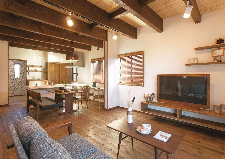住まいるコーポレーション【デザイン住宅、自然素材、インテリア】ダークトーンでまとめたLDKは床や梁、造作家具を自然塗料で着色し、落ち着きと重厚感を演出。造作のTVボードは宙に浮かせたデザインで掃除も楽々。見た目だけでなく機能性も考慮されている