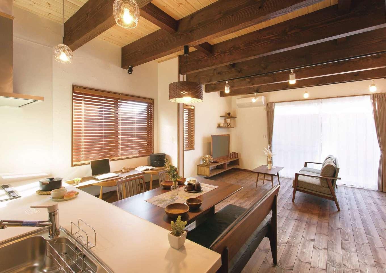 住まいるコーポレーション【デザイン住宅、自然素材、インテリア】キッチンからはリビングダイニングや続き間の和室まで見渡せる。パインの板張りの天井はあえてナチュラル色にして梁の存在感を強調した