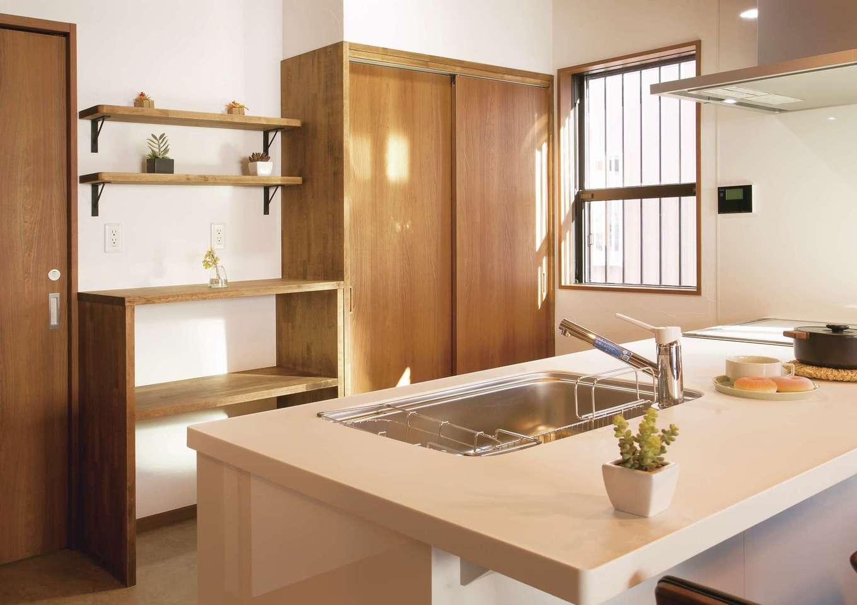 住まいるコーポレーション【デザイン住宅、自然素材、インテリア】ワイドなカウンタートップのオープンキッチン。背面の収納は床と同色で統一。生活感の出るものは大きな扉で「隠して収納」、オシャレな器類は棚に飾って「見せる収納」と、収納方法を上手に使い分けている