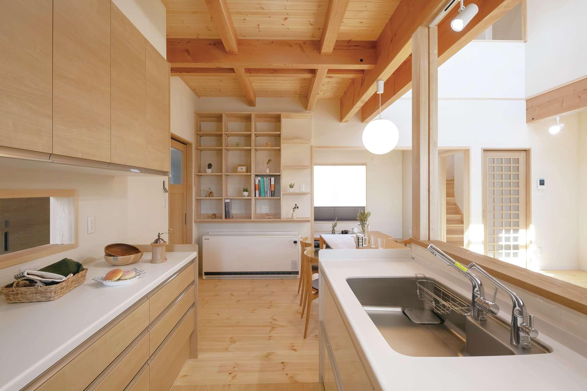 住まいるコーポレーション【収納力、自然素材、デザイン住宅】キッチンの横にはセンスの良い「見せる収納棚」を設けてある。その下には蓄熱暖房機があり、1台で家中が温まり家計にも優しい。吹抜けの解放感を強調するために、キッチンの天井はあえて低めに設定
