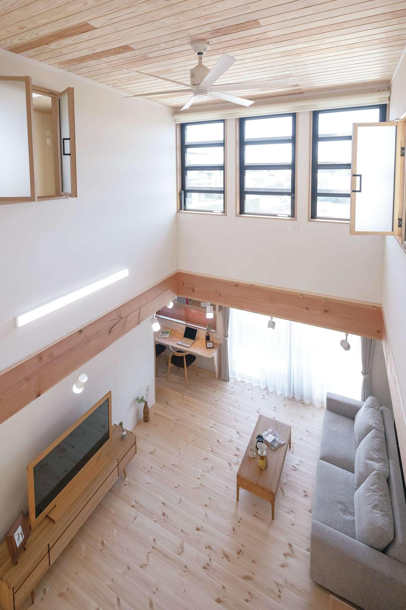 住まいるコーポレーション【収納力、自然素材、デザイン住宅】吹抜けと無垢板張りの勾配天井が、圧倒的な開放感をもたらすLDK。2階の各室に室内窓を設けてあるので、窓を開ければ風が家中に巡り、1階にいる家族との会話も弾む