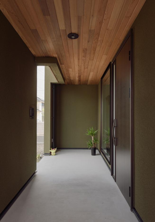 R+house藤枝(西遠建設)【デザイン住宅、建築家、インテリア】モスグリーンの外壁の裏面には玄関ポーチを横長に広々と確保。フィックスの窓の奥に見えるのは土間のディスプレイコーナー
