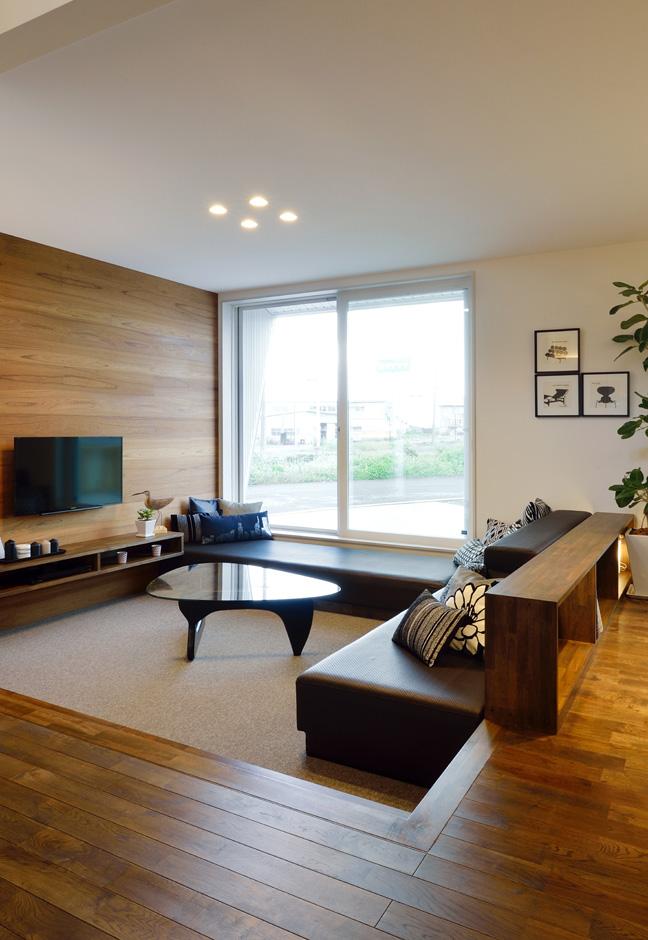 R+house藤枝(西遠建設)【デザイン住宅、建築家、インテリア】段差で空間を緩やかにゾーニングし、独特の「囲まれ感」が居心地の良さをもたらすステップダウンリビング。ウォルナットのアクセントウォールが落ちつきのある雰囲気を醸し出す。掃出し窓の先にはウッドデッキがある
