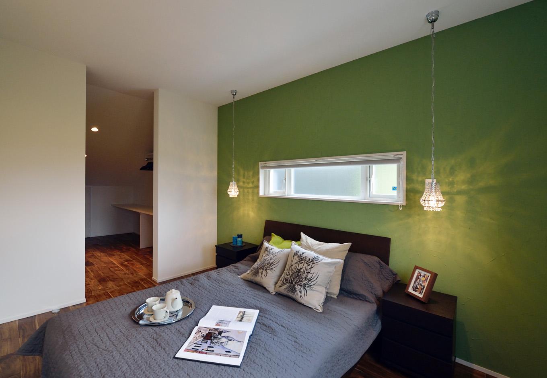 R+house藤枝(西遠建設)【デザイン住宅、建築家、インテリア】落ち着きのあるグリーンのアクセントウォールが安らぎをもたらす2階の寝室。ウォークインクローゼットには充分な広さを確保し、その奥は小屋裏へとつながっている