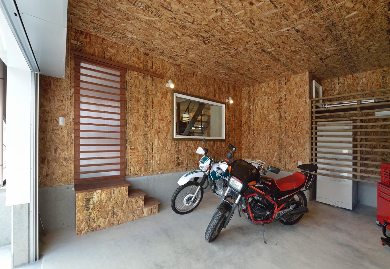 R+house藤枝(西遠建設)【デザイン住宅、建築家、インテリア】構造用合板を表しにしたビルトインガレージ。窓の先は玄関となっていて、その隣に直接出入りができるドアも設けてある