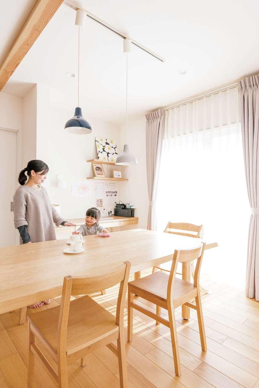 四季彩ひだまり工房 高田工務店【デザイン住宅、子育て、間取り】キッチンと横並びのダイニングは日当たり良好。無印良品の塩カラーなペンダントライトがアクセントに。奥に家事&スタディコーナーを造作