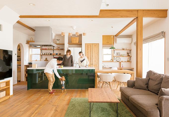 四季彩ひだまり工房 高田工務店【輸入住宅、自然素材、インテリア】セピアグリーンのキャビネットが差し色になったアイランドキッチンは、バックヤードに木の収納棚を造作し、食器や雑貨を見せることでカフェっぽい雰囲気に。造作のダイニングテーブルを真横にレイアウトしたことで、配膳も片づけも楽々。娘さんも積極的にお手伝いするようになった