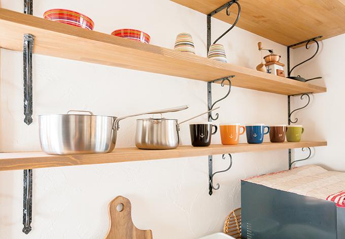 四季彩ひだまり工房 高田工務店【輸入住宅、自然素材、インテリア】スペイン漆喰の白い壁に無垢の棚とアイアンが映える。お気に入りの食器や雑貨をディスプレイして、料理タイムをより楽しく。水回りへの動線もスムーズで、奥さまの家事時間を短縮できる