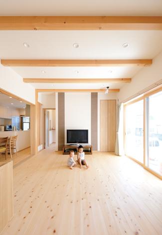 四季彩ひだまり工房 高田工務店【子育て、二世帯住宅、間取り】庭に面した子世帯のリビング。肌触りのいい床は無垢のヒノキ、現しの梁は杉材を使用。テレビステーションは調湿効果の高いエコカラットを採用