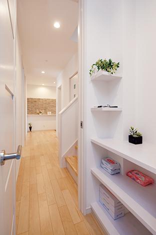 四季彩ひだまり工房 高田工務店【子育て、収納力、二世帯住宅】玄関からキッチンまで一直線に繋がる廊下。デッドスペースはすべて収納棚を造作