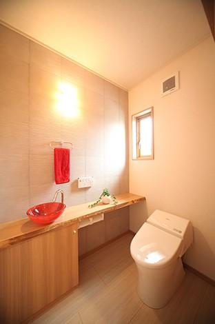 四季彩ひだまり工房 高田工務店【子育て、収納力、自然素材】リビングに採用した消臭効果のあるエコカラットをトイレにも取り入れた。陶器の手洗いボウルがアクセントに