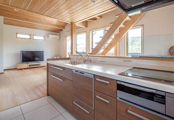 四季彩ひだまり工房 高田工務店【子育て、二世帯住宅、自然素材】キッチンからはリビングと、窓の外の緑を一望できる。床には水に強いフロアタイルを使用