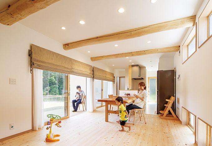 四季彩ひだまり工房 高田工務店【子育て、自然素材、間取り】庭と雑木林の緑を望むLDK。天井には松の化粧梁、床は天竜ひのきを使い、無垢材で造作した家具が馴染む。羊毛断熱の吸湿効果で、室内は常に快適