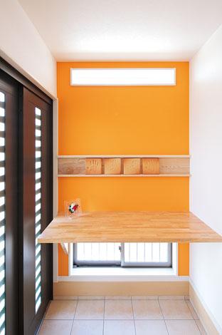 四季彩ひだまり工房 高田工務店【子育て、収納力、自然素材】暗くなりがちな玄関ホールは小窓をたくさん設けて採光を確保。オレンジ色の壁には新築記念の手形を飾ってアクセントを