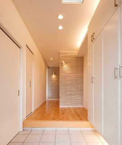 四季彩ひだまり工房 高田工務店【デザイン住宅、収納力、自然素材】納戸+シューズクローゼットで玄関収納は完璧。ホールの一部にタイル壁を採用。間接照明が玄関をよりオシャレに演出