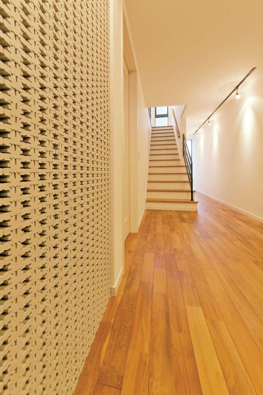 高級感あふれるミャンマーチークの床に合わせて壁面に立体タイルを張り、スタイリッシュなイメージに仕上げた玄関ホール。トップライトから落ちる光が2階のLDKへといざなうかのよう。スポットライトが当たる壁面はホームギャラリーとしても使える贅沢な空間