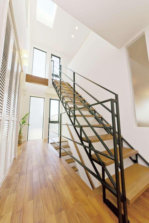 トップライトからの柔らかな光と吹抜けの開放感が気持ちいい2階ホール。鉄骨階段の手すりはオブジェのような存在感があり、白い空間のアクセントに。大容量の壁面収納も共働き夫婦にはありがたい