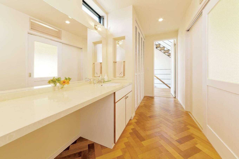 ネイルサロンとつながるパウダールームは、ヘリンボーン張りの床を採用。ホテルライクな鏡とワイドなカウンターはデザインと実用性を両立。ハイサイドライトからの光が、北側とは思えない明るさをもたらす