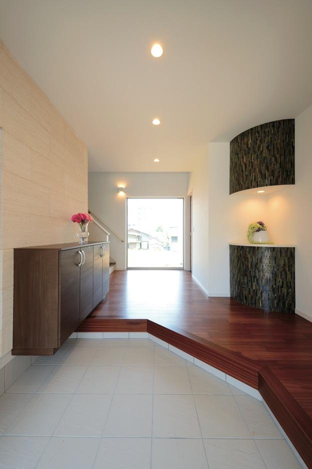 幸和ハウジング【デザイン住宅、収納力、二世帯住宅】美術館をイメージした玄関ホール。名古屋モザイクの装飾が空間に彩りを添える。正面奥の窓越しに視界が抜けてより広く感じられる