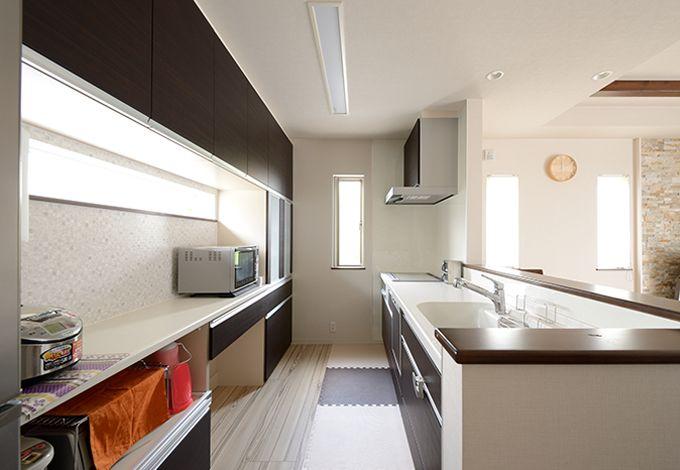 収納力抜群のキッチンは背面も広々。長めの収納カウンターが重宝
