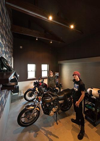 幸和ハウジング【デザイン住宅、趣味、ガレージ】ご主人が最もこだわったガレージに夫妻のバイクが並ぶ。12 畳の広さに加え床を下げたため予想以上の大空間に仕上がった。レンガを積み上げたような壁紙もユニーク